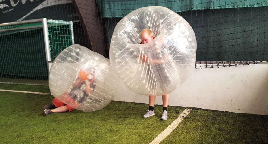 Erschöpfte Teilnehmer beim Indoor Bubble Soccer